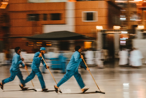 janitorial workers sweeping floors quickly at the airport to prevent disruption